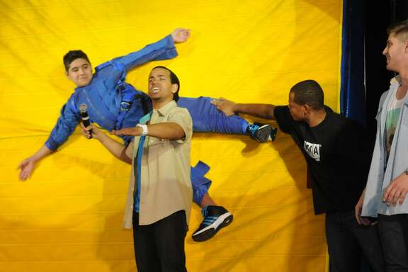 Kenneth Leal, 12, left, gets velcro-walled during a Newtonís Three Laws of Motion demonstration  presented by John James, center, of Atlanta and the Forces in Motion Live cast at Wunderlich Intermediate School in Klein.