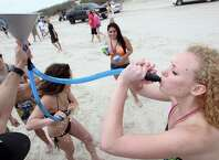 Olivia Rodriguez, of Corpus Christi, left, spits out the beer as Meghan Lawler, of Austin, drinks from the beer bong, Tuesday, March 11, 2014, during spring break on the beach in Port Aransas, Texas. Sun and warmer weather brought out bigger crowds at beaches across the Coastal Bend.