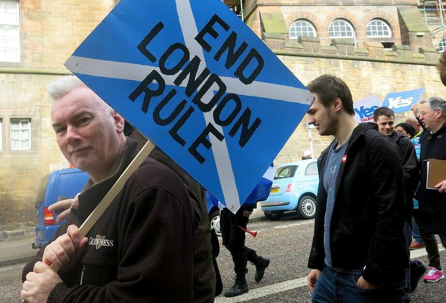 "In this photo taken March 15, 2014 a man carries a placard during a pro-independence march in Edinburgh, Scotland for the upcoming vote on Scotland's independence from the United Kingdom.  Scotland's swithering ""middle million"" has Britain's future in its hands. ""Swithering"" means wavering, and it's a word you hear a lot in Scotland right now. Six months from Tuesday, Scottish voters must decide whether their country should become independent, breaking up Great Britain as it has existed for 300 years. Faced with the historic choice, many find their hearts say ""aye"" but their heads say ""why risk it?"" Polls suggest as many as a quarter of Scotland's 4 million voters remain undecided, and their choice will determine the outcome. Many long to cut the tie binding them to England, but fear the risks _ and the financial fallout. (AP Photo/Jill Lawless) Photo: Jill Lawless, Associated Press"