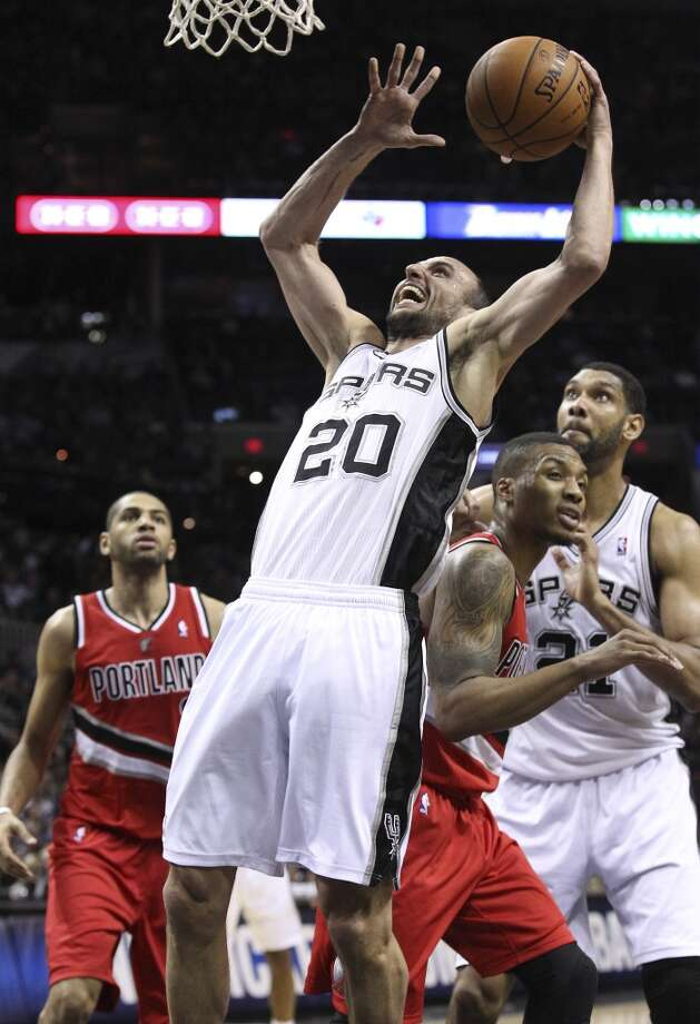 Spurs' Manu Ginobili (20) struggles to put up a shot against Portland Trailblazers' Damian Lillard (00) in the first half at the AT&T Center on Wednesday, March 12, 2014. Photo: Kin Man Hui, San Antonio Express-News
