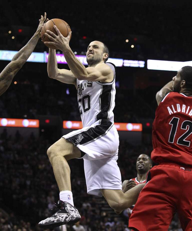 Spurs' Manu Ginobili (20) drives the pan against Portland Trailblazers' LaMarcus Aldridge (12) in the first half at the AT&T Center on Wednesday, March 12, 2014. Photo: Kin Man Hui, San Antonio Express-News