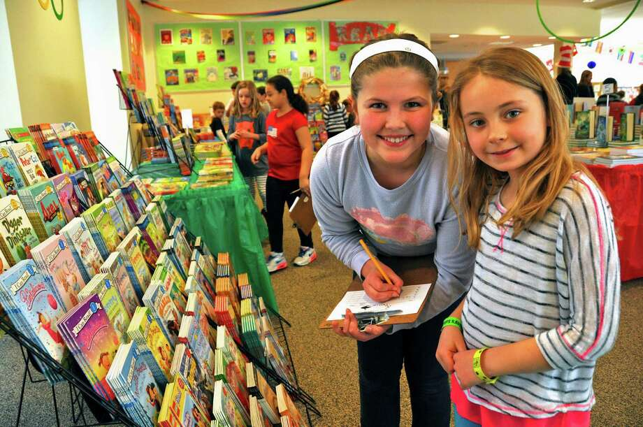 Tokeneke School fourth-grader Brooke Edwards goes shopping with her first-grade buddy Isabel Hurkala during the school's annual book fair. Photo: Contributed Photo, Contributed / Darien News