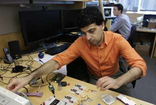 Mozziyar Etemadi works on a smart diaphragm device with Alex Heller (background) in San Francisco, Calif. on Friday, March 14, 2014. The team of engineers at the UCSF Mission Bay campus are developing a wireless device that they hope will detect early signs of pre-term births in pregnant women.