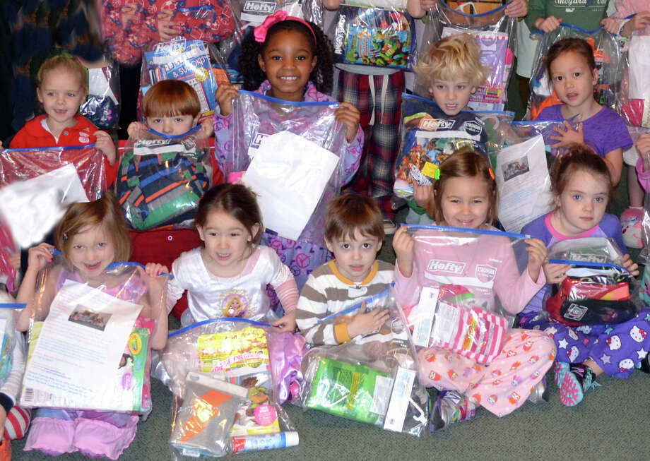 """A Pair to Share,"" the annual service project for Darien's Pear Tree Point School pre-kindergarten and kindergarten students, provides nighttime supplies for the Boys and Girls Village in Bridgeport. In front row from left, Daphne Upson, Peyton Eckert, Luke Schwandt, Lulu Hurley and Matilda Davenport. Back row, Lucy Logan, Cody Bloom, Maddison Stevens, Gavin Murphy and Tatum Jaroch. Photo: Contributed Photo, Contributed / Darien News"