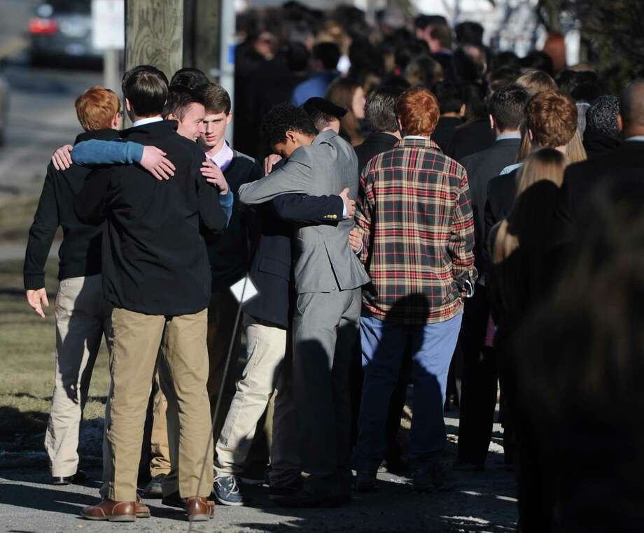 Friends of Emma Sandhu hug while waiting in line outside of Kane Funeral Home in Ridgefield, Conn. for the wake of the 15-year-old Ridgefield sophomore on Tuesday, March 18, 2014.  Sandhu died Friday night after she was struck by a car on Ridgebury Road in Ridgefield with a group of other teens.  Sandhu's funeral is scheduled for Wednesday at 10:30 a.m. in St. Elizabeth Seton Church, 520 Ridgebury Road, Ridgefield, with the Rev. Joseph A. Prince officiating. Photo: Tyler Sizemore / The News-Times