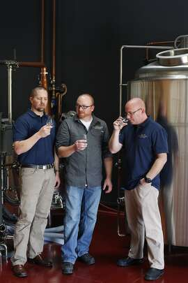 Eric Larimer, (l-r) Ryan Sutherland and Barry Sutherland, who together constitute Sutherland Distilling Company, pose for a portrait between their still, left, and mash tun, right, on March 13, 2014 in Livermore, Calif. Eric, Ryan and Sutherland, are director of sales and marketing, distiller, and CFO, respectively.