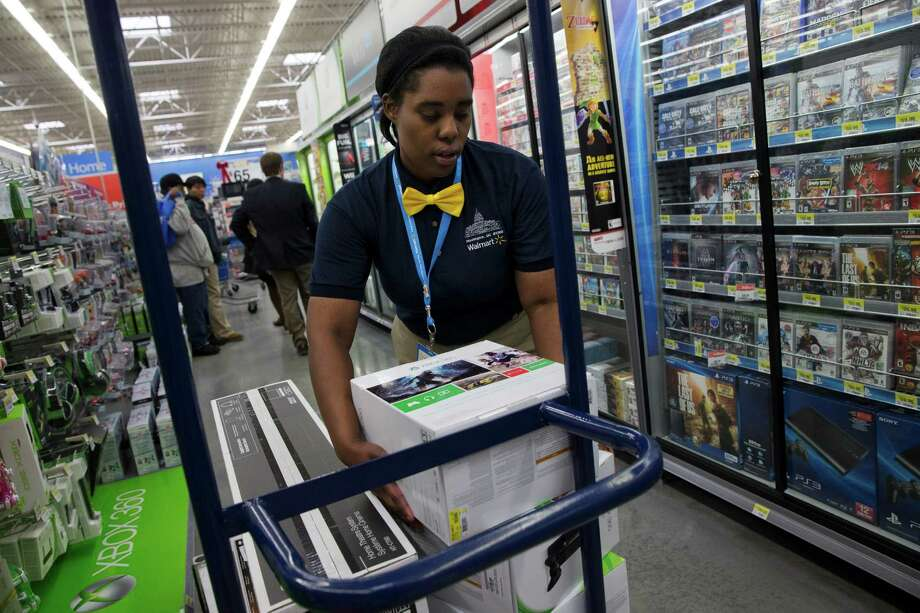 FILE -  In this Wednesday, Dec. 4, 2013, file photo, Tracey Anderson, 26, re-stocks X-Box sets on opening day of a new Wal-Mart on Georgia Avenue Northwest in Washington. Wal-Mart plans to expand its video game trade-in program to its stores, offering store credit for thousands of video games.The world's largest retailer plans to let video game owners trade in used video games online and in Wal-Mart stores for store credit but not cash. The credit can be used in both Wal-Mart and Sam's Club stores. Previously they offered trade-ins on a more limited basis online.  (AP Photo/Jacquelyn Martin, File) ORG XMIT: NYBZ130 Photo: Jacquelyn Martin / AP