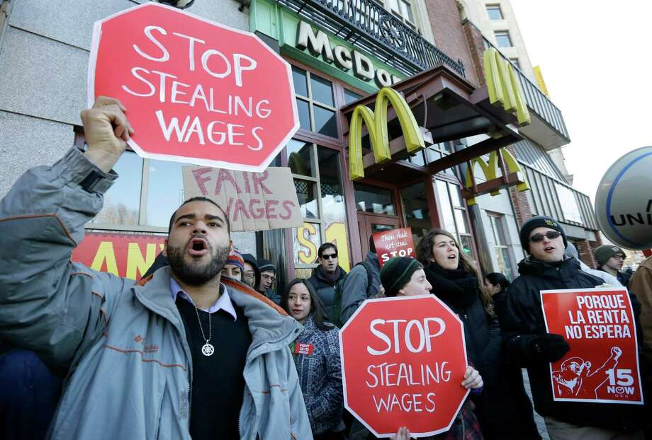 Demonstrator Zev Nicholson, of Boston, left, holds a placard and chants during a protest outside a McDonalds fast foot restaurant, Tuesday, March 18, 2014, in Boston, held to call attention to the denial of overtime pay and other violations protesters say deprive workers of the money they're owed. (AP Photo/Steven Senne) ORG XMIT: MASR101 Photo: Steven Senne / AP