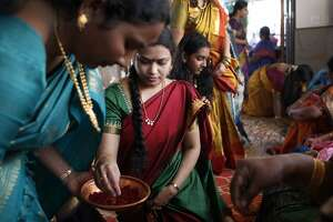 Tulasi Gurrala takes part in a Sri Lalitha Sahasranama Archana ceremony by applying a bindi to another devotee at Shiva-Vishnu Temple on March 15, 2014 in Livermore, Calif.