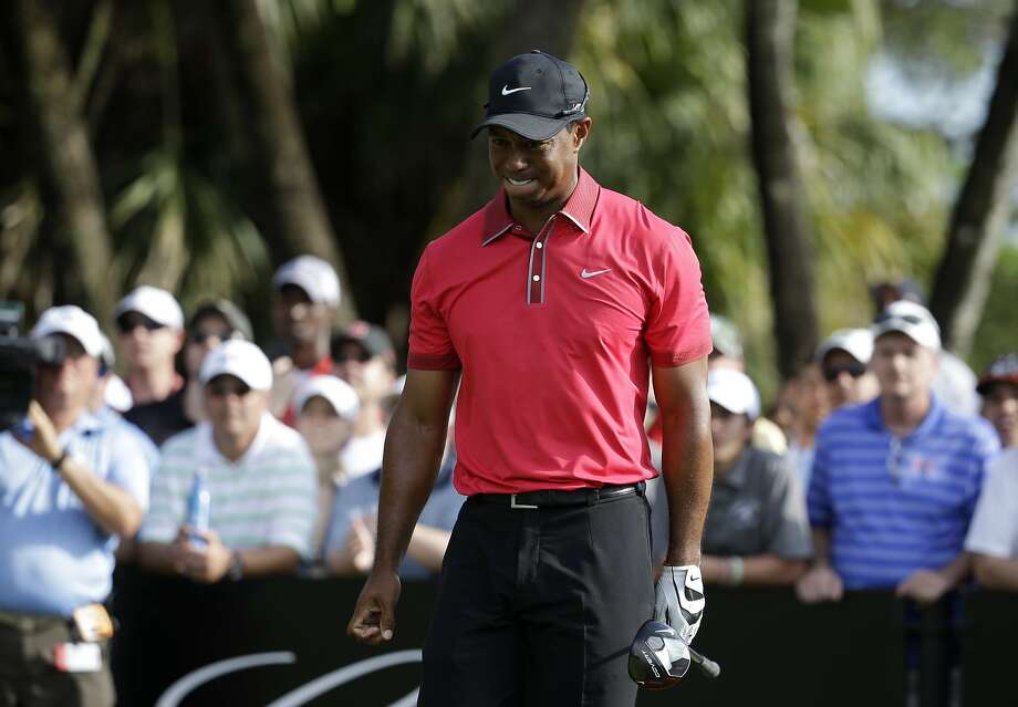 Tiger Woods grimaces after teeing off on the 12th hole during the final round of the Cadillac Championship golf tournament Sunday, March 9, 2014, in Doral, Fla. Woods' back was flaring up after hitting out of a bunker on the sixth hole. (AP Photo/Lynne Sladky) Photo: Lynne Sladky, Associated Press
