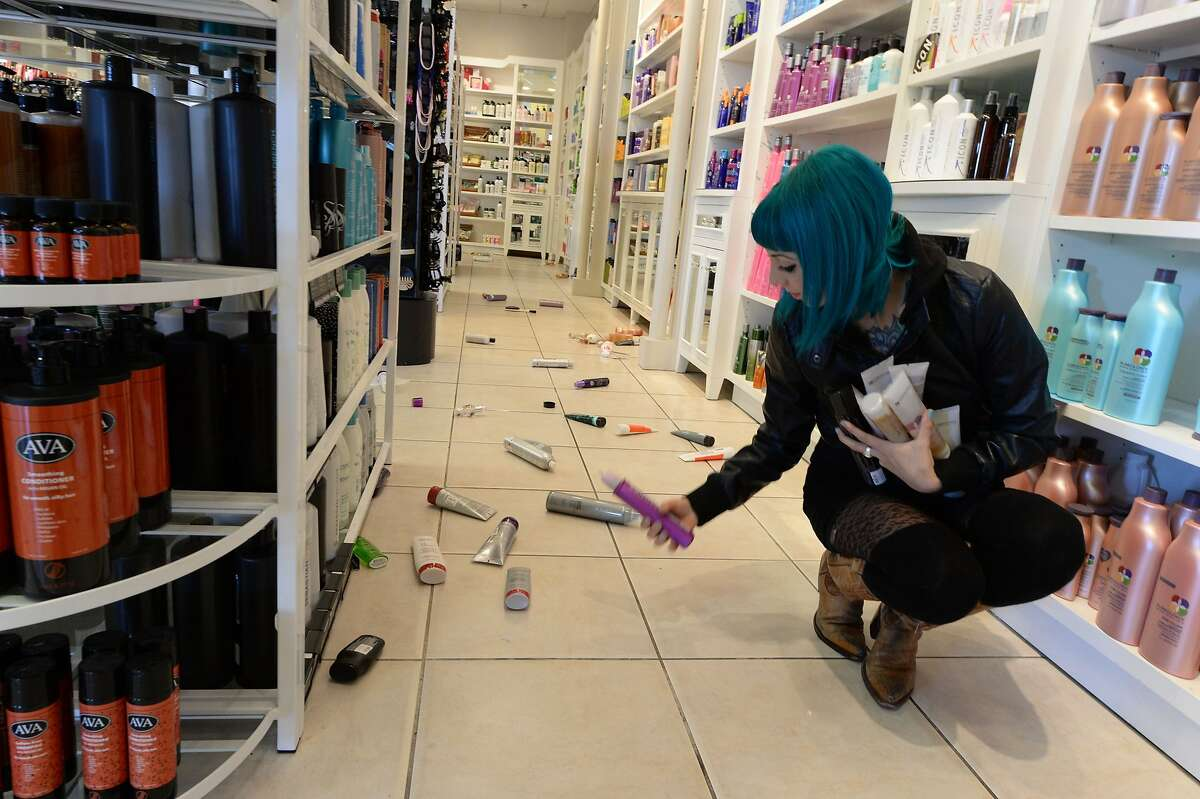 Employee Paula Anania cleans up hair care products that were knocked off the shelf in a beauty supply store in the Encino area of Los Angeles after a 4.4 earthquake jolted the area March 17, 2014. Burglar alarms went off and a few objects fell off shelves after the temblor, which struck just before dawn some 20 miles northwest of the West Coast city. AFP PHOTO / ROBYN BECKROBYN BECK/AFP/Getty Images