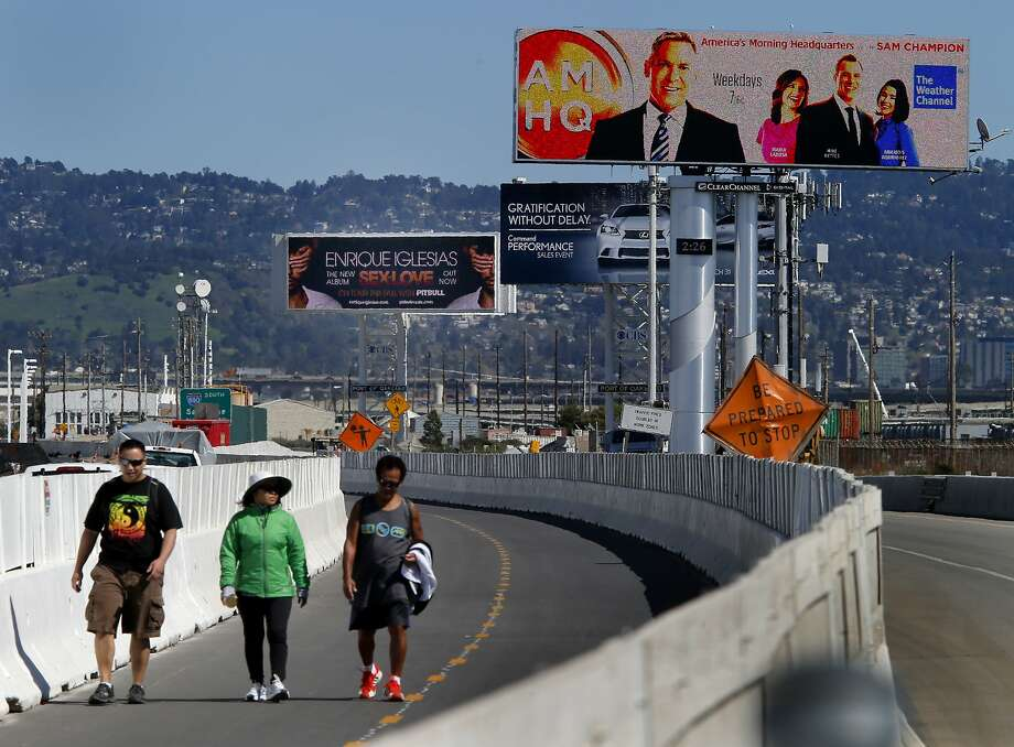 Three digital billboards loom over walkers at the Oakland end of the Bay Bridge. The group Scenic East Bay is urging Caltrans to block a plan to install three more ad screens alongside the ramp to Interstate 880. Photo: Brant Ward, The Chronicle