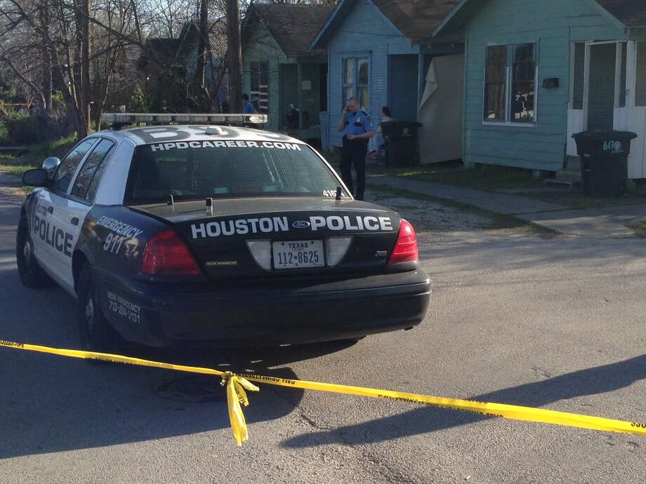 Officers investigate at the scene of the shooting Tuesday afternoon at a home along Stevens near Campbell, just north of downtown. Photo: Mike Glenn, Houston Chronicle