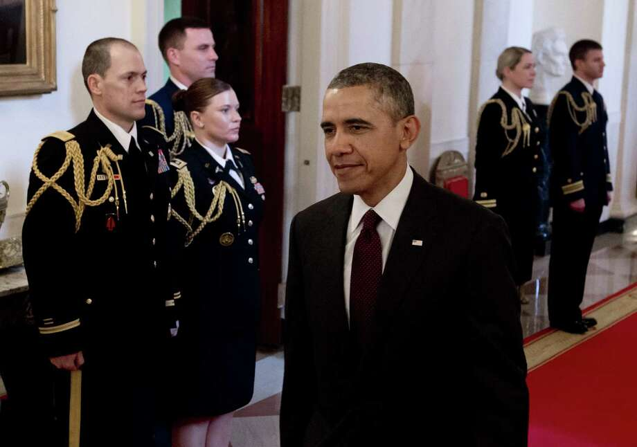 President Barack Obama arrives for a Medal of Honor ceremony in the East Room of the White House in Washington on March 18, 2014. Obama awarded the Medal of Honor to 24 veterans, 3 of whom are still living, who fought in World War II, the Korean War and the Vietnam War, most of whom were previously denied the prestigious honor due to their Hispanic, black or Jewish backgrounds. The ceremony results from a Pentagon review of Jewish and Hispanic war records ordered by Congress in 2002. Photo: SAUL LOEB, AFP/Getty Images / AFP