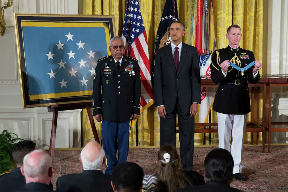 Staff Sgt. Melvin Morris (left) stands with President Barack Obama before being awarded the Medal of Honor during a ceremony in the East Room of the White House on Tuesday, March 18, 2014, in Washington. Photo: Evan Vucci, Associated Press / AP