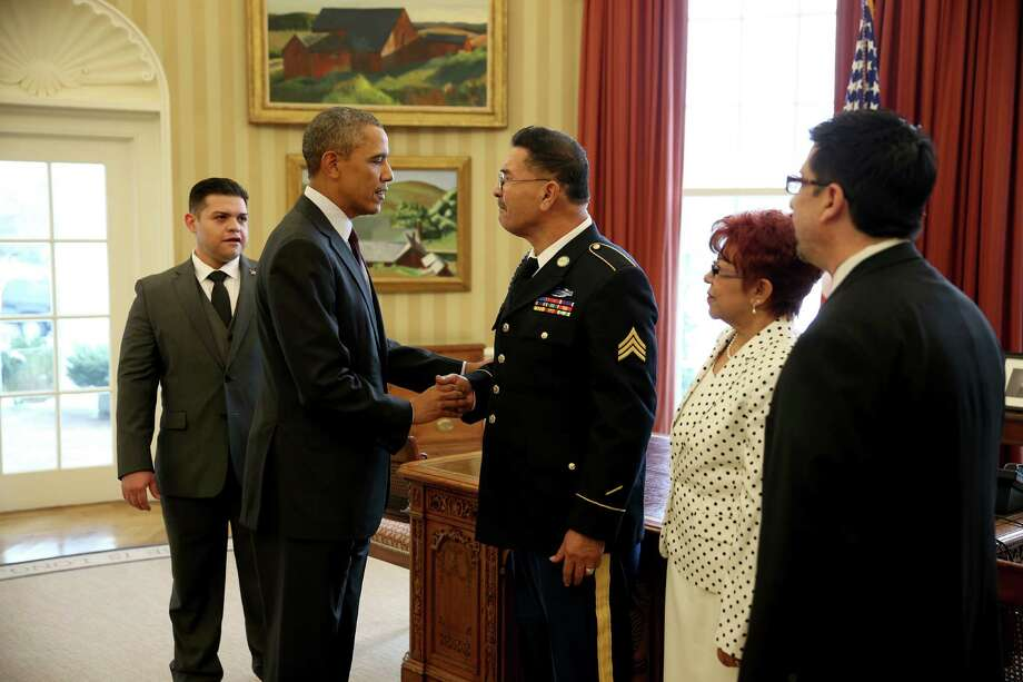 President Barack Obama speaks with U.S. Army Specialist Four (Ret.) Santiago J. Erevia, a Vietnam War veteran, in the Oval office before presenting him with the Medal of Honor at a ceremony in the White House on March 18, 2014 in Washington. Photo: Joe Raedle, Getty Images / 2014 Getty Images