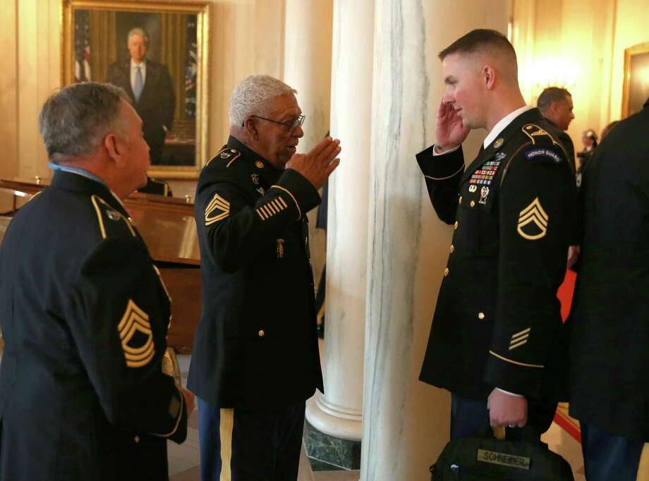 U.S. Army Staff Sgt. (Ret.) Melvin Morris (left), a Vietnam War veteran, is saluted by U.S. Army Staff Sergeant Christopher Schneider, from U.S. Army Old Guard, 3d U.S. Infantry Regiment, after a ceremony presenting Morris with the Medal of Honor in the White House on March 18, 2014 in Washington. Photo: Joe Raedle, Getty Images / 2014 Getty Images