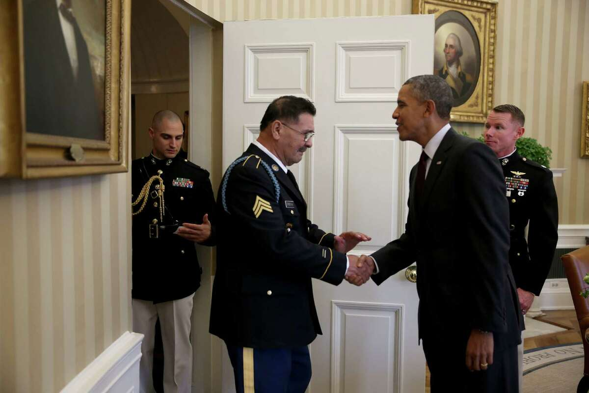 President Barack Obama greets U.S. Army Specialist Four (Ret.) Santiago J. Erevia, a Vietnam War veteran, in the Oval office before presenting him with the Medal of Honor at a ceremony in the White House on March 18, 2014 in Washington.