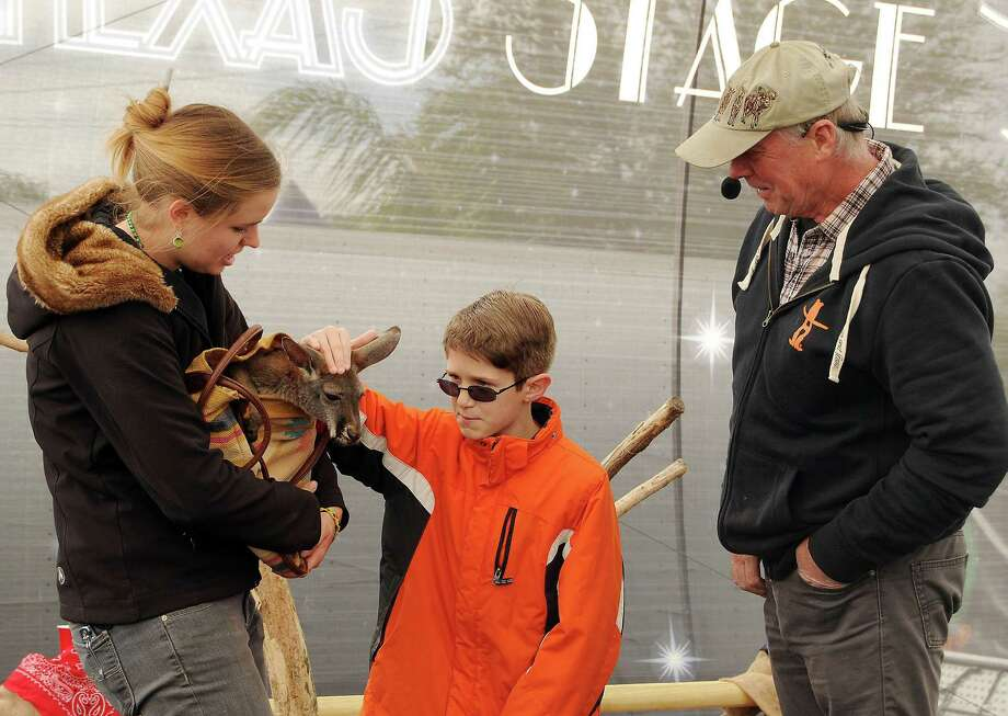 Alexander Little pets a baby kangaroo in a bag held by Emily Coil during the Amazing Animals show on the Stars Over Texas Stage at the Houston Livestock Show & Rodeo Monday March 17, 2014. Photo: Dave Rossman, For The Houston Chronicle / Freelance