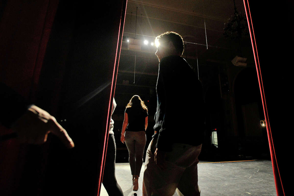 Seniors Donal Ryan walks out on stage with his date Kirsi Balazs while Alexi Nikolopoulos, center, walks to the front of the stage as Lisa Rich, left, motions for the next couple to hit their mark during the Fashion Show fundraiser dress rehearsal at the Stamford High School auditorium in Stamford, Conn., on Tuesday, March 18, 2014. Members of the senior and junior class will show off their fashions from four local vendors on Thursday at 7 p.m. at the high school. Half of the proceeds will benefit the senior class prom after-party, which is June 6, and the other half of the proceeds go towards next year's after-prom party.