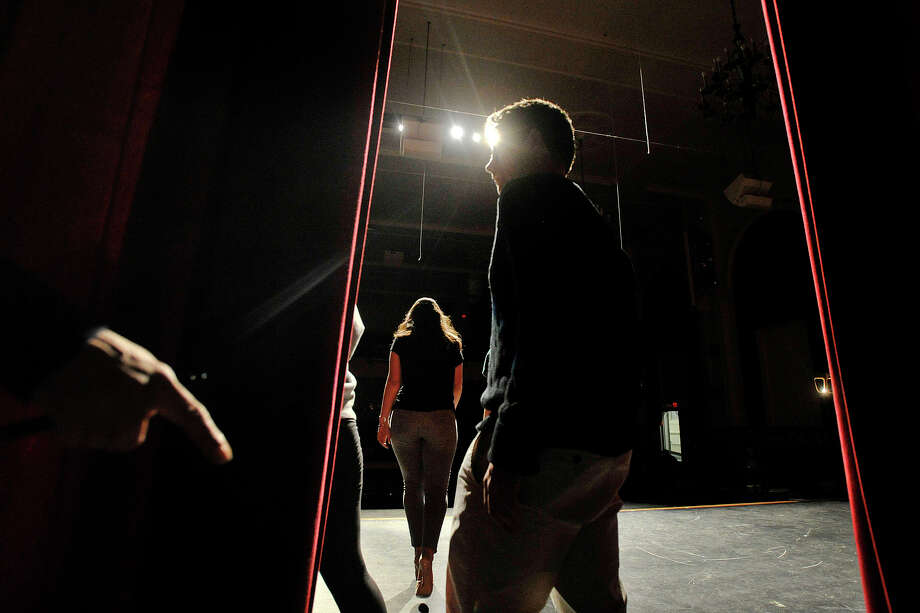 Seniors Donal Ryan walks out on stage with his date Kirsi Balazs while Alexi Nikolopoulos, center, walks to the front of the stage as Lisa Rich, left, motions for the next couple to hit their mark during the Fashion Show fundraiser dress rehearsal at the Stamford High School auditorium in Stamford, Conn., on Tuesday, March 18, 2014. Members of the senior and junior class will show off their fashions from four local vendors on Thursday at 7 p.m. at the high school. Half of the proceeds will benefit the senior class prom after-party, which is June 6, and the other half of the proceeds go towards next year's after-prom party. Photo: Jason Rearick / Stamford Advocate