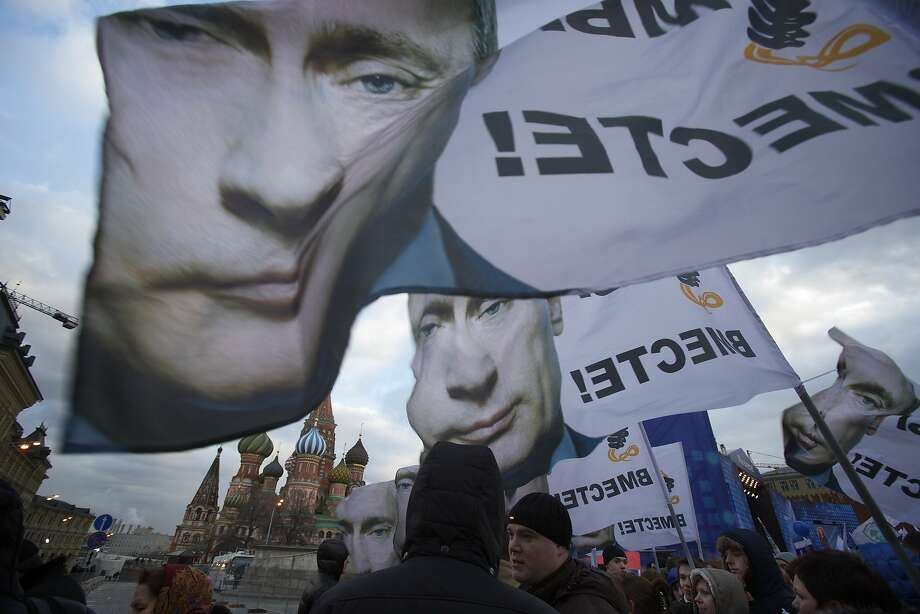 "People rally in support of Crimea joining Russia, with banners and portraits of Russian President Vladimir Putin, reading ""We are together,"" in Red Square in Moscow, Tuesday, March 18, 2014.  With a sweep of his pen, President Vladimir Putin added Crimea to the map of Russia on Tuesday, describing the move as correcting past injustice and responding to what he called Western encroachment upon Russia's vital interests. (AP Photo/Pavel Golovkin) Photo: Pavel Golovkin, Associated Press"
