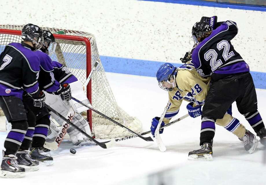 Newtown High School's #28 Dominic Cartelli takes aim on Tri-Town goal during Tuesday evening Division III State Tourament at Ingallis Rink in New Haven. Photo: Mike Ross / Mike Ross Connecticut Post freelance -www.mikerossphoto.com