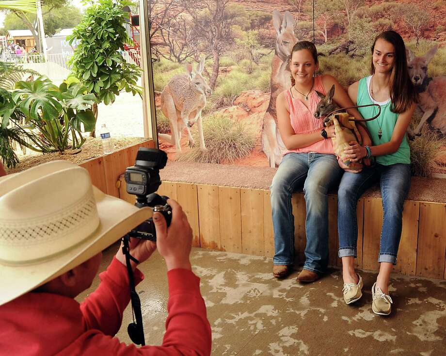 Taylor Butler and Alyssa Maki have their photo taken with a baby kangaroo at Mark Schoebel's booth at the rodeo Saturday  March 15, 2014. Photo: Dave Rossman, For The Houston Chronicle / Freelance