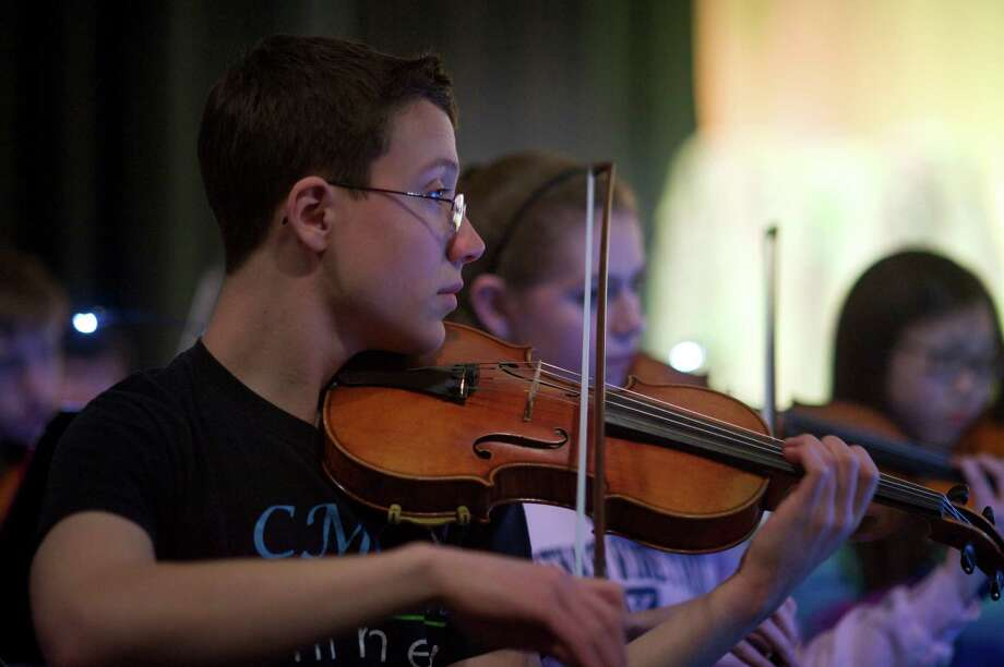 "Kai Hedin, 1st violinist, during the dress rehearsal for the Newtown High School production of ""Peter Pan' on Tuesday night, March 18, 2014. Behind Hedin is Anna Pinckney. Photo: H John Voorhees III / The News-Times Freelance"