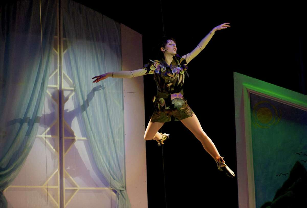 Peter Pan, played by Victoria Madden, shows Wendy, Michael and John how to fly, during the dress rehearsal for the Newtown High School production of