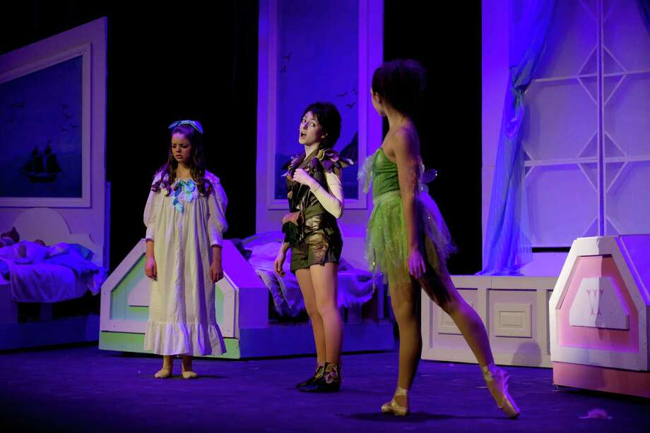 "Peter Pan, played by Victoria Madden, stands between Wendy, left, played by Lexi Tobin, and Tinkerbell, played by Lauren Russo, during the dress rehearsal for the Newtown High School production of ""Peter Pan' on Tuesday night, March 18, 2014. Photo: H John Voorhees III / The News-Times Freelance"