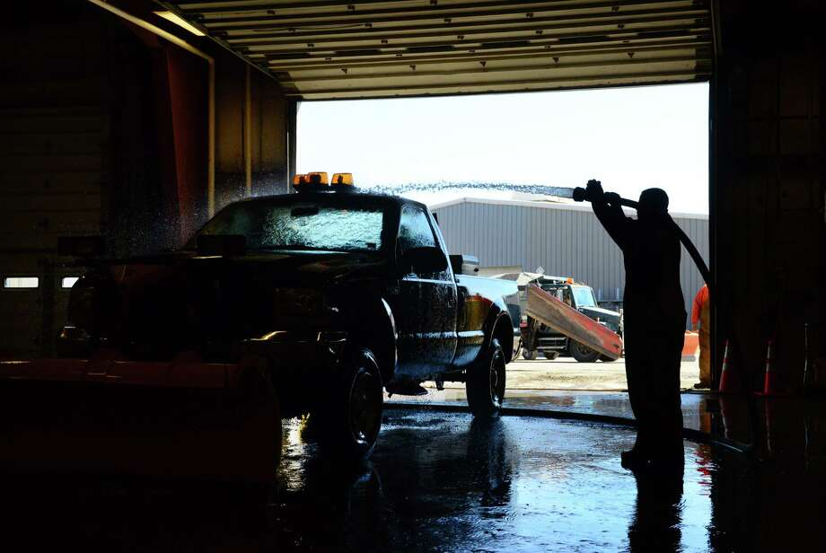 Town of Colonie highway maintenance worker Trevor Norman of Colonie washes down one of the town's snowplow equipped pickup trucks Tuesday morning, March 18, 2014, at the town garage on Old Niskayuna Road in Colonie, N.Y. (Will Waldron/Times Union) Photo: WW