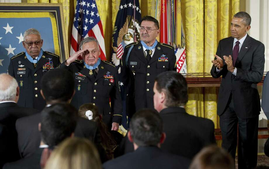 President Barack Obama applauds the three newest living Medal of Honor recipients, from left, Army Staff Sgt. Melvin Morris, Army Sgt. 1st Class Jose Rodela, and Army Spc. 4 Santiago Erevia during Tuesday's White House ceremony. Photo: SAUL LOEB, Staff / AFP