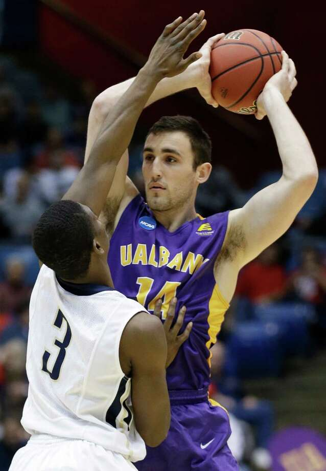 Albany forward Sam Rowley (14) is pressured by Mount St. Mary's guard Sam Prescott (3) in the first half of a first-round game of the NCAA college basketball tournament, Tuesday, March 18, 2014, in Dayton, Ohio. (AP Photo/Al Behrman) ORG XMIT: OHAB129 Photo: Al Behrman / AP