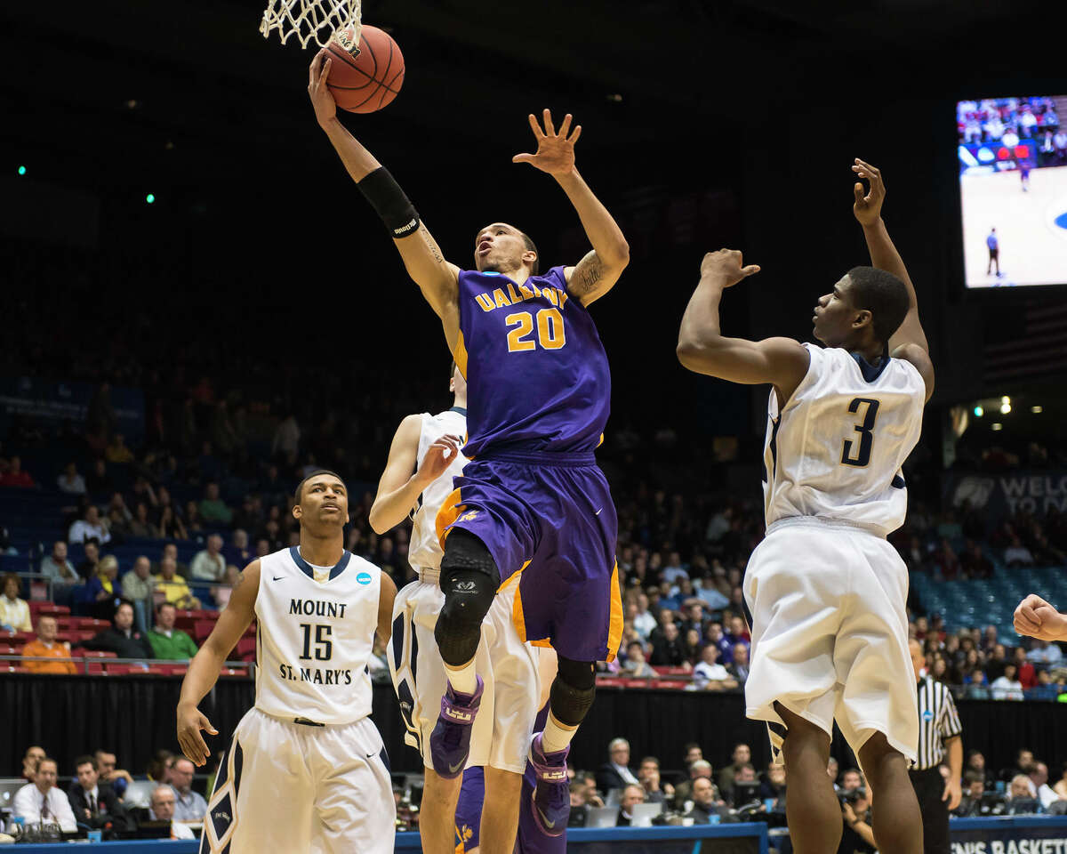 UAlbany Great Danes forward Gary Johnson (20) center, puts up the leaping shot from the paint with Mount St Mary's Mountaineers guard Sam Prescott (3) right anNCAA first round game, Tuesday night, Mar. 18, 2014, in Dayton, O.H. (Gregory Fisher/Special to the Times Union)
