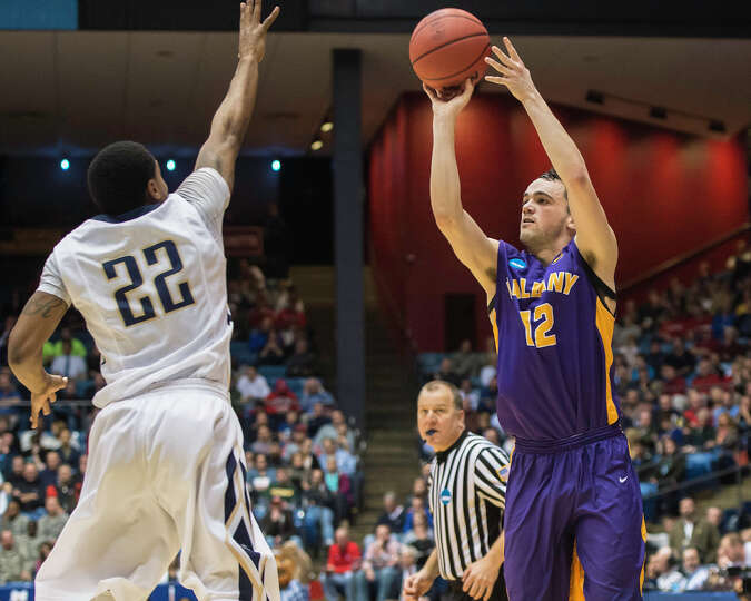 UAlbany Great Danes guard Peter Hooley (12) puts up an outside shot against Mount St Mary's  Mountai