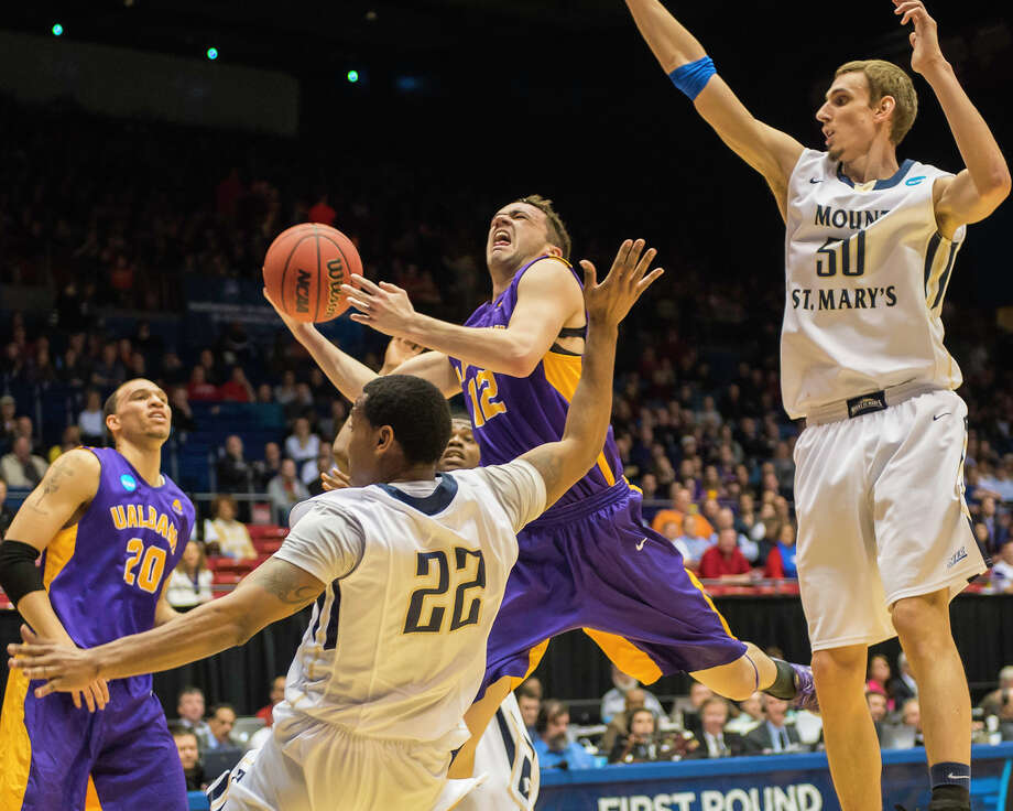 UAlbany Great Danes guard Peter Hooley (12) puts up a leaping shot against Mount St Mary's  Mountaineers guard Rashad Whack (22) left and Mount St Mary's  Mountaineers center Taylor Danaher (50) right during the NCAA first round game, Tuesday night, Mar. 18, 2014, in Dayton, O.H. (Gregory Fisher/Special to the Times Union) Photo: GF / 00025174A