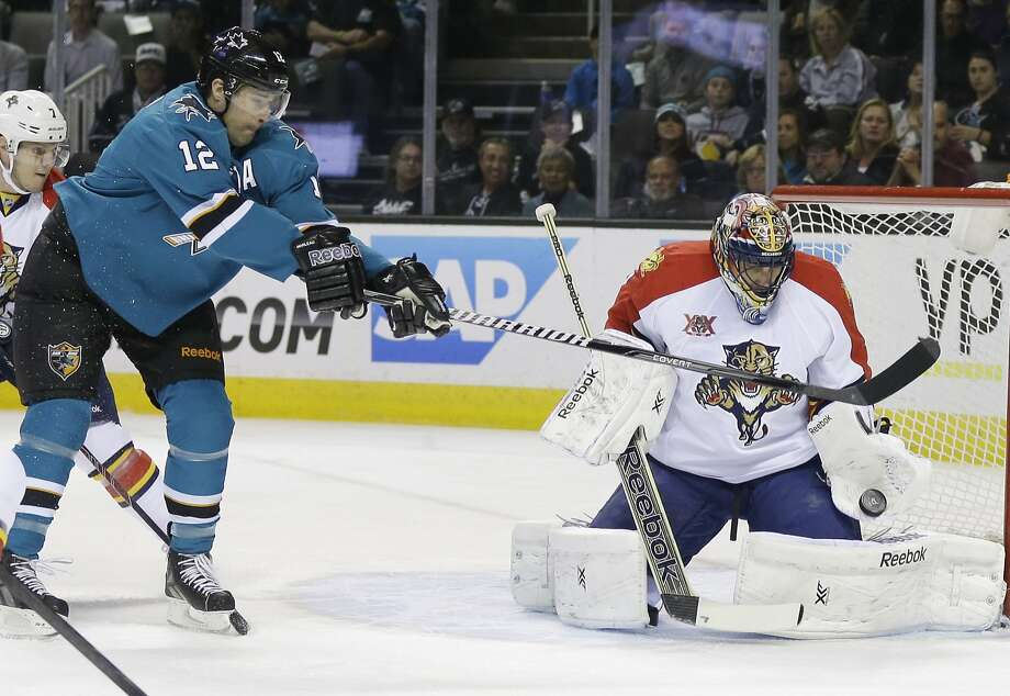 Florida's Roberto Luongo, who made 52 saves, stops a shot despite the efforts of the Sharks' Patrick Marleau. Photo: Marcio Jose Sanchez, Associated Press