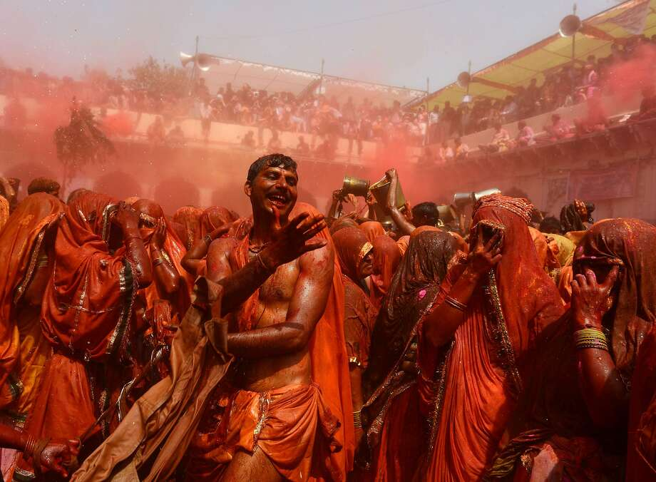 TOPSHOTS Indian revellers take part in the game of 'Huranga' at The Dauji Temple in Mathura, some 100kms south of New Delhi on March 18, 2014. 'Huranga' is a game played between men and women a day after Holi, the festival of colours, during which men drench women with liquid colours and women tear off the clothes of the men.  AFP PHOTO/ Chandan KHANNAChandan Khanna/AFP/Getty Images Photo: Chandan Khanna, AFP/Getty Images