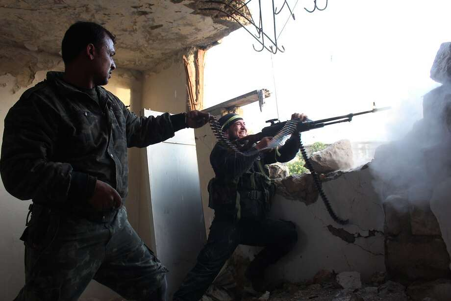 Rebel fighters fire a machine gun during clashes with pro-government forces on March 18, 2014 in the northern Syrian city of Aleppo. The regime planes bombed Aleppo today, killing at least four people, including two children, according to the Syrian Observatory for Human Rights.     TOPSHOTS/AFP PHOTO/AMC/TAMER AL-HALABITAMER AL-HALABI/AFP/Getty Images Photo: Tamer Al-halabi, AFP/Getty Images