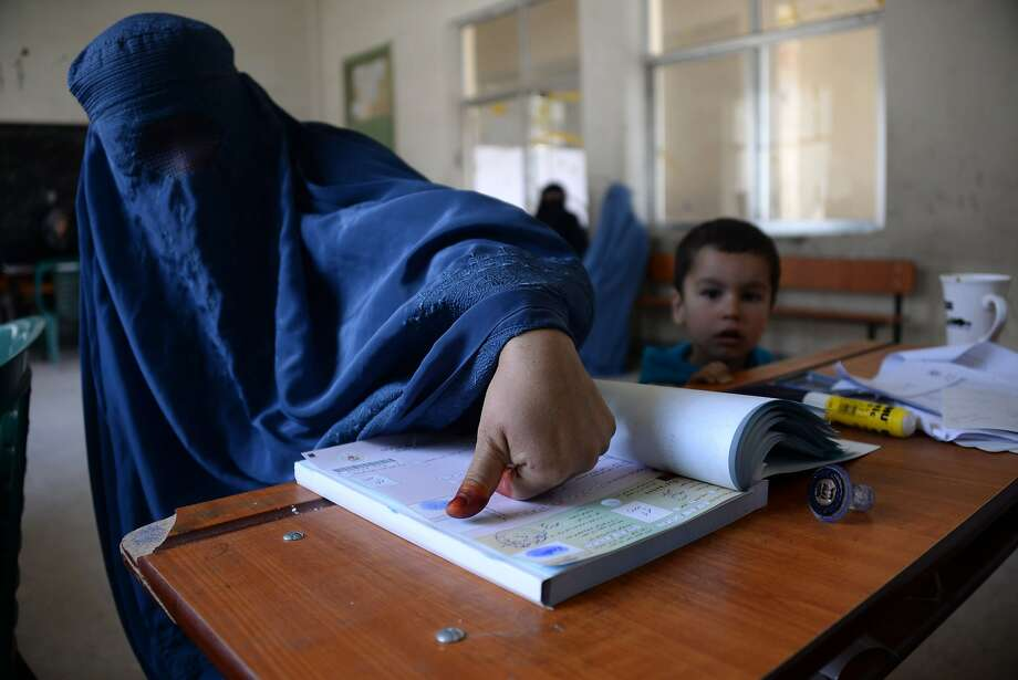 An Afghan resident marks a page with her thumb-print as she registers to vote at a regsitration centre in Mazar-i-Sharif on March 18, 2014.  Afghanistan is due to hold presidential and provincial council elections in April this year. AFP PHOTO/FARSHAD USYANFARSHAD USYAN/AFP/Getty Images Photo: Farshad Usyan, AFP/Getty Images