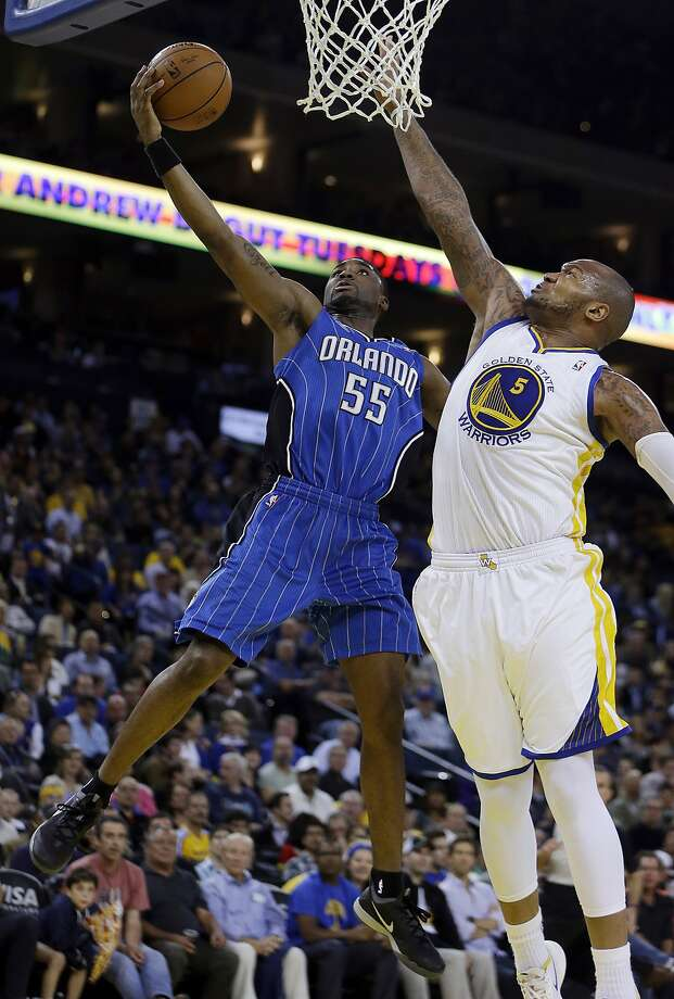 Orlando Magic guard E'Twaun Moore, left, lays up a shot against Golden State Warriors' Marreese Speights (5) during the first half of an NBA basketball game Tuesday, March 18, 2014, in Oakland, Calif. (AP Photo/Ben Margot) Photo: Ben Margot, Associated Press