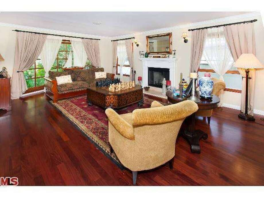 The formal living room has a fireplace. Photo: Photo By MLS