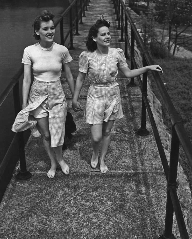 Three women crossing a footbridge, circa 1945. They are wearing matching gingham outfits. Photo: FPG/Archive Photos, Getty Images