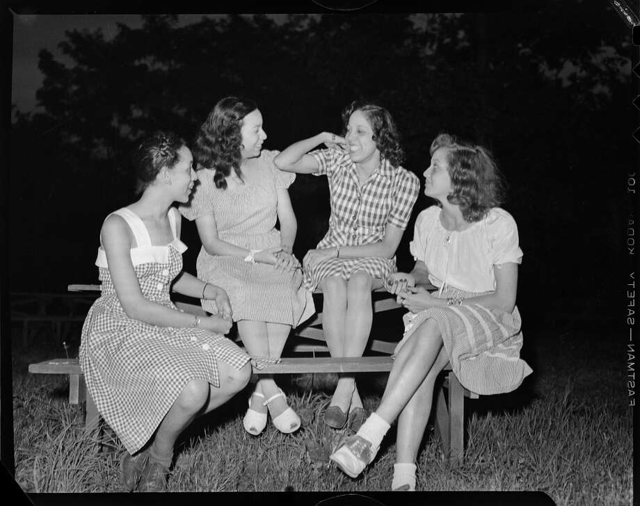 Group portrait of four women, including two wearing gingham dresses, and one on right wearing saddle shoes, gathered around a picnic table for the Alpha Phi Alpha picnic, Allegheny County, Pennsylvania, July 1945. Photo: Teenie Harris Archive/Carnegie M, Getty Images