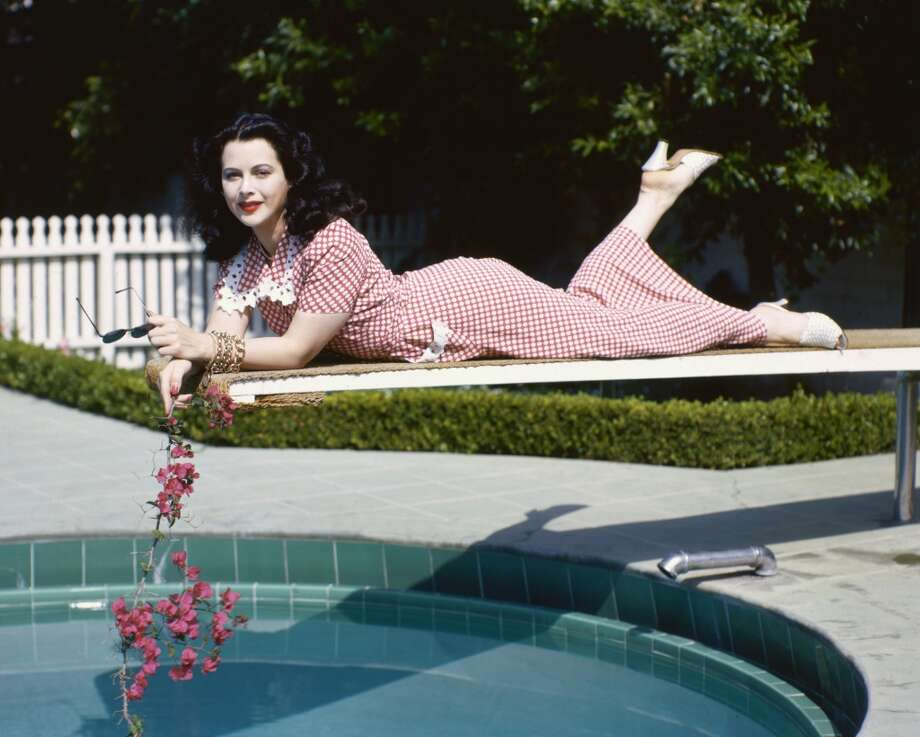 Hedy Lamarr (1913-2000), Austrian actress, wearing a red gingham dress and holding a branch with pink flowers while leaning, front down, on a diving board over the water of a swimming pool against velour-covered surface, 1945. Photo: Silver Screen Collection, Getty Images