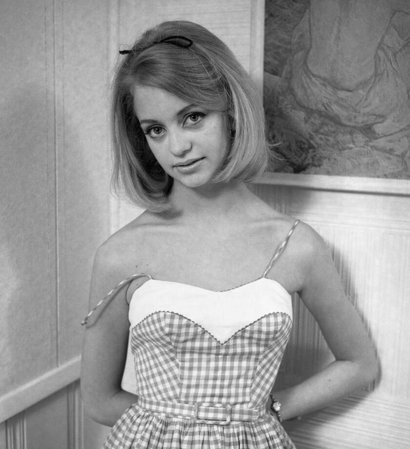 Portrait of American actress Goldie Hawn as she poses, arms behind her back, in a gingham summer dress, Arlington, Virginia, September 8, 1964. Photo: Joseph Klipple, Getty Images