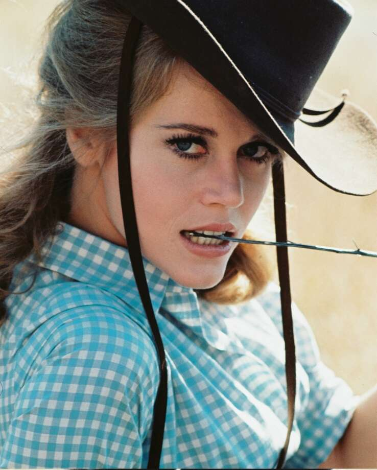 "Jane Fonda wearing a black cowboy hat and blue gingham shirt, posing with a twig between her teeth, in a publicity portrait issued for the film, ""Cat Ballou,"" 1965. Photo: Silver Screen Collection, Getty Images"