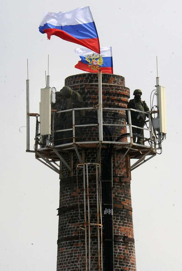 A Russian soldier patrols on a chimney adorned with Russian flags at the Ukrainian navy headquarters in the Crimean city of Sevastopol. Photo: Viktor Drachev, AFP/Getty Images