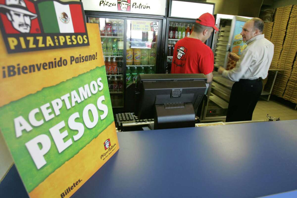 A sign saying that Mexican Pesos are accepted is shown as Angel Vargas, left, and Antonio Swad check on a cooler at a Pizza Patron store in Dallas, Wednesday, Jan. 10, 2007. Death threats and hate mail poured in almost as soon as the pizza chain's new promotion rolled out: accepting Mexican pesos as well as U.S. currency as payment. Officials at Dallas-based Pizza Patron say they weren't trying to inject themselves into a larger political debate about illegal immigration when they posted signs Monday saying Aceptamos pesos _ We accept pesos _ at their 59 stores across five states: Texas, Colorado, Arizona, Nevada and California.